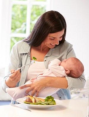 New mother holding her newborn eating a healthy dinner
