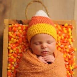 swaddled newborn baby wearing candy corn hat