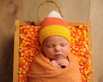 swaddled newborn baby wearing candy corn hat