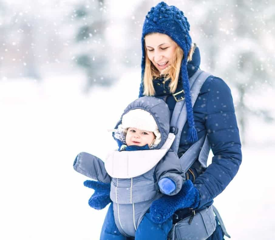mom bundled with baby in the snow playing