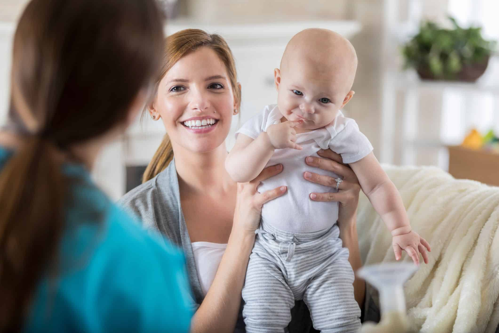 mom holding baby talking with sleep consultant